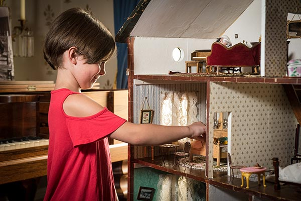 Girl playing in doll house at the hands-on exhibit