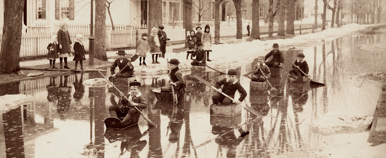 Boys paddling down a flooded street in makeshift boats