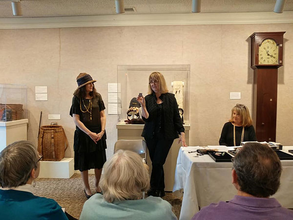 Woman presented artifacts to audience in Chapman Museum exhibit