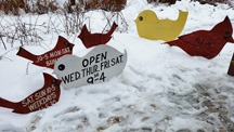 little painted wooden birds in snow