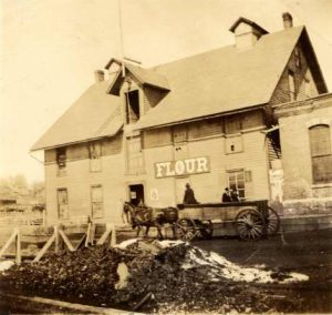 wooden building with sign for flour