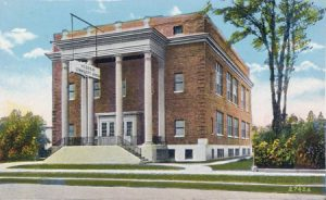 color postcard of brick building with 2-story white columns