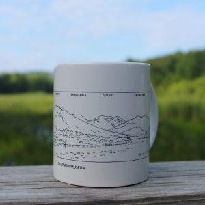 white mug with a sketch of mountains