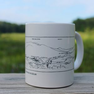 white mug with sketch of mountain scene